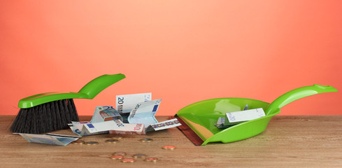 Sweeps money in the shovel on colorful background close-up