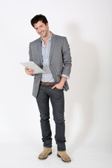 Young man standing on white background with tablet