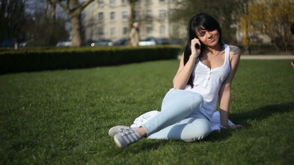 Young woman talking on the phone in the grass