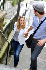 Young romantic couple climbing stairs in town