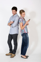 Young couple standng back to back with mobilephone