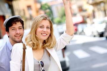 Young couple hailing for a taxi cab