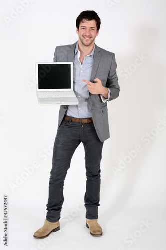 Young businessman pointing at laptop screen