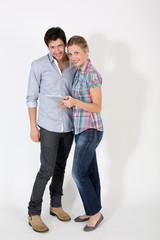 Young couple on white background holding digital tablet