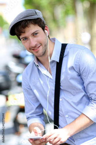 Young trendy guy talking on mobilephone in the street