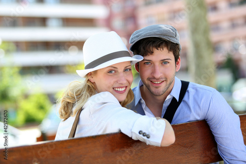 Lovely young couple sitting on public bench