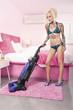 Sexy young tattooed woman in bikini vacuuming bedroom
