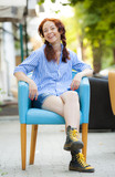 Funny hipster girl in chair on the street poster
