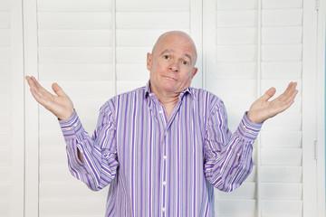 Portrait of a senior man shrugging shoulders in confusion