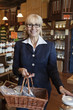 Portrait of a happy senior owner standing with basket full of spices in store