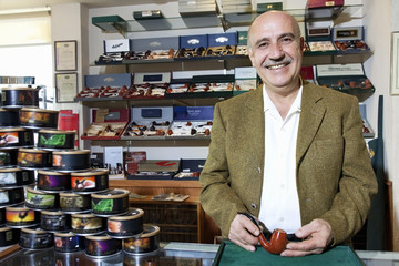 Portrait of a happy mature tobacco shop owner with cans on display