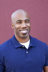 Portrait of a happy bald African American male over colored background