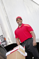 Cheerful young delivery person pushing handtruck