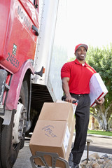 Young African American male standing with packages near delivery truck