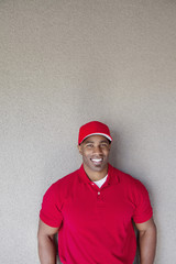 Portrait of a happy African American delivery man against wall