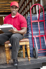 Portrait of a happy delivery man sitting on chair with clipboard