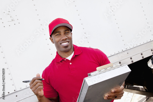 Portrait of a happy African American man holding clipboard with delivery truck in background
