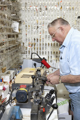 Side view of senior locksmith making key in store