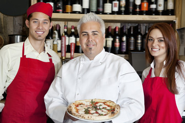 Portrait of a happy chef holding pizza with wait staff