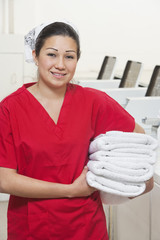 Portrait of a happy female employee in red uniform holding towel
