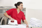 Happy young female employee ironing while looking away in Laundromat