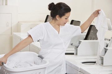 Young female employee putting clothes in washing machine