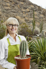 Portrait of a senior gardener holding potted cactus plant