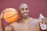 Portrait of an African American athlete with basketball and water bottle over colored background