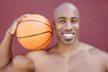 Portrait of a young African American man with basketball on shoulder over colored background