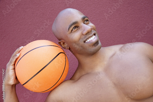 Young African American man with basketball on shoulder looking away over colored background
