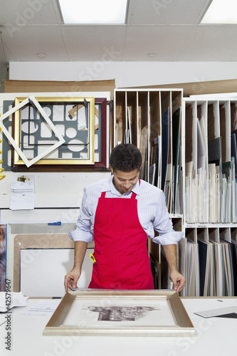 Young skilled worker adjusting frame on photograph