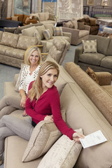 Portrait of a happy mother and daughter in furniture store