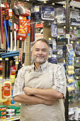 Portrait of a confident mature store clerk with arms crossed in hardware shop