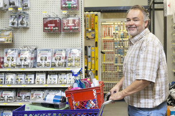 Side view portrait of a happy mature man with shopping cart in hardware store