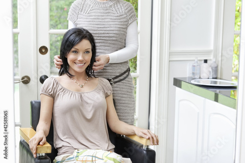 Happy beautiful mid adult woman with hairstylist in background