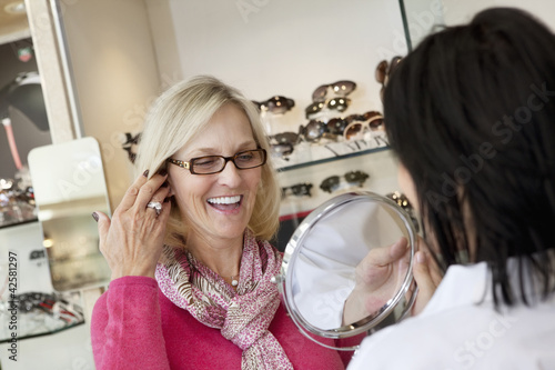 Cheerful senior woman trying on glasses while optician holding mirror