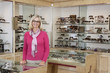 Portrait of a happy senior female optician standing in store