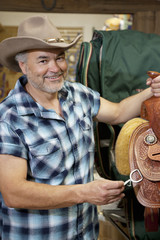 Portrait of a happy cowboy with riding tack in feed store