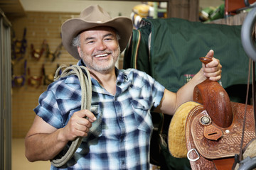 Happy mature cowboy with saddle and rope in feed store