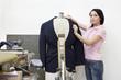 Portrait of a mid adult woman dressing mannequin