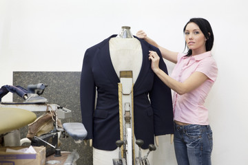 Portrait of a mid adult woman dressing mannequin