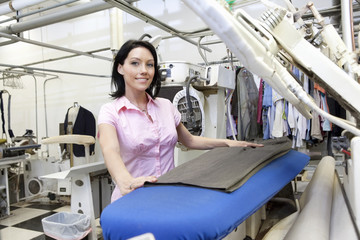 Portrait of a happy mid adult woman standing by ironing machine in laundry