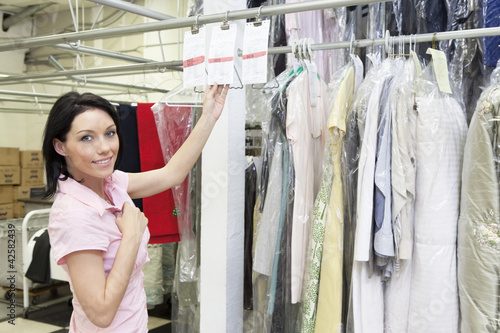 Portrait of a mid adult woman standing by clothing rack