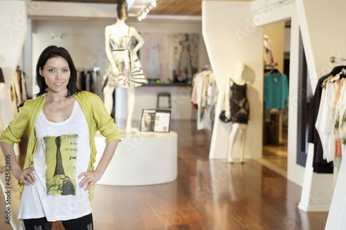 Portrait of a happy mid adult woman standing with hands on hips in fashion clothing store