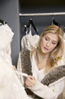 Beautiful young woman looking at price tag of wedding dress in bridal store