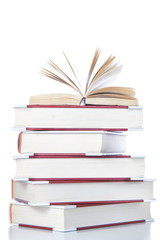 Open book on stack of books. On a white background.