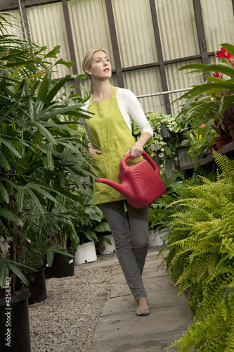 Young woman with watering can in greenhouse