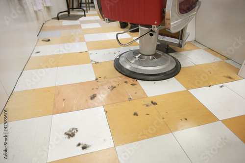 An empty barber shop with cut hair on floor