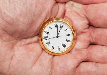 Brass small watch or clock in palm of hand