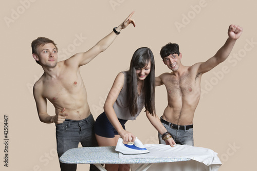Shirtless men with woman ironing shirt over colored background